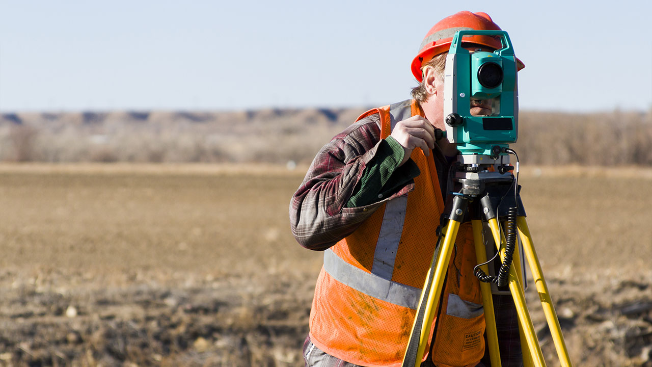 Land surveyors measuring existing railroad bridge in rural area
